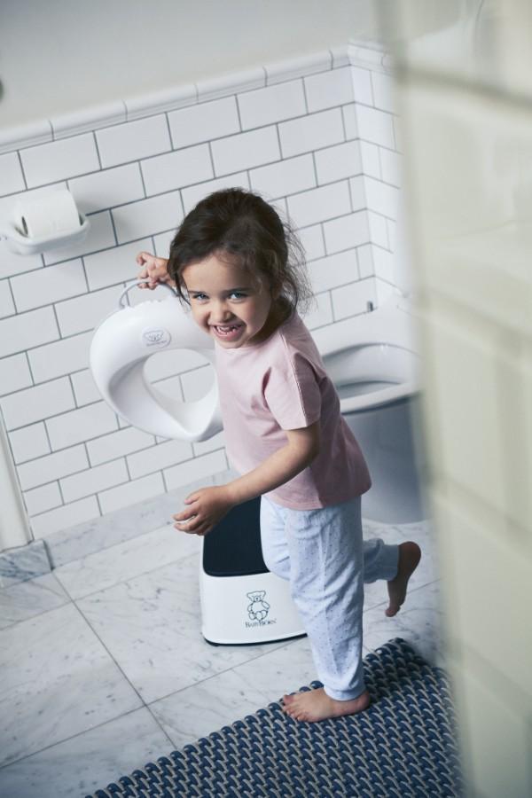 Réducteur de Toilette BABYBJÖRN, Blanc/Noir en situation enlevé par l'enfant vue de loin