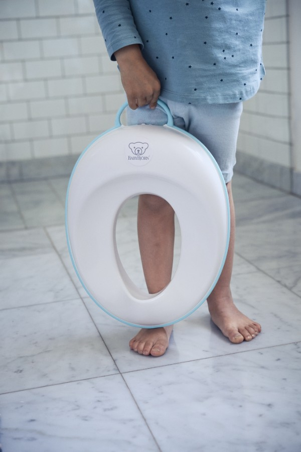 Réducteur de Toilette BABYBJÖRN, Blanc/Noir en situation porté par l'enfant