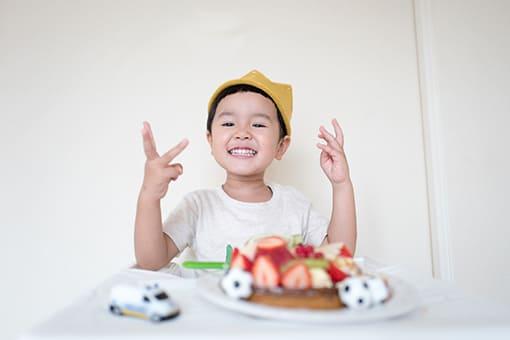enfant riant devant un gâteau aux fraises - page d'accueil de Bambinou - encart d'abonnement à la newsletter de Bambinou
